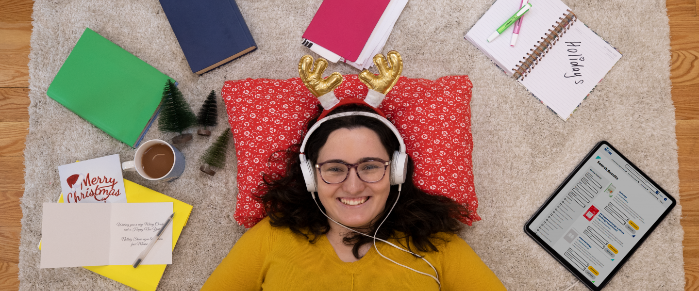 Girl wearing headphone listening to an audio book in Christmas antlers