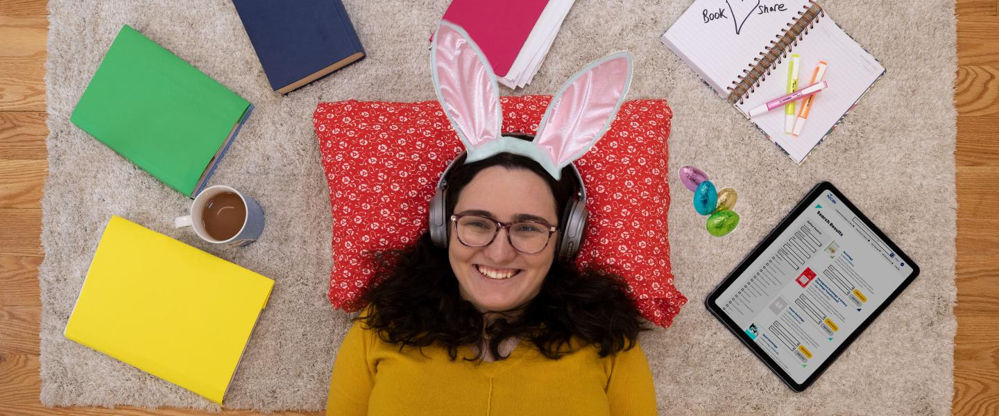 girl listening to audio book with headphones on her iPad on whist wearing Easter rabbit ears